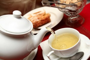 tetera y taza con té en una mesa